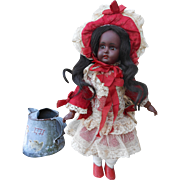 A sweet, 12,8 inches mulatto Kestner doll with wonderful clothing.