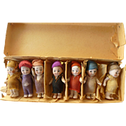 A bunch of seven vintage tiny Googlys in their original box