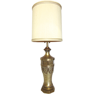 Details: Oversized carved mid-century modern lamp by Marbro (Italy- circa 1960's) finished in a burnished gold with subtle orange and brown undertones. This piece has an octagonal base and a geometric shield pattern mid-body and geometric, distressed