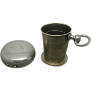 A novelty collapsible beaker in a 'fob watch' case. c 1880