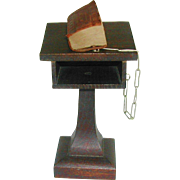 A miniature Bible on an oak lectern.   c 1911