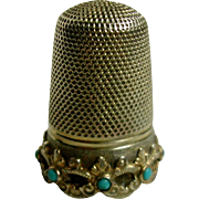 A 9 carat gold thimble set with turquoise stones. c 1860