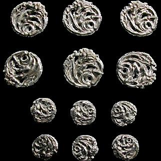 A set of 12 Edwardian pierced silver buttons. c1900