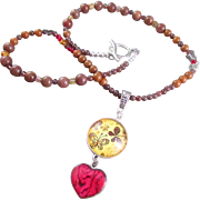 A Glass Dome Pendant with Butterfly and Sandstone Gemstone Necklace and Earrings