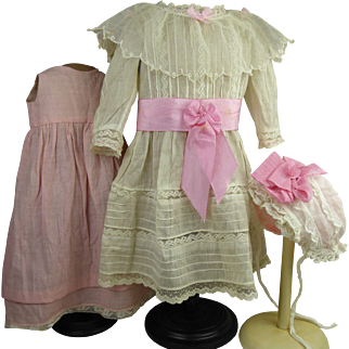 Three-piece ensemble : original antique French white batiste dolls dress with tucks and lace, including pink under dress and  matching bonnet, appr. 1900.