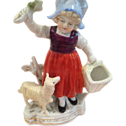 German girl, teasing her lamb figurine