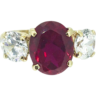 14k Yellow Gold ring with a synthetic ruby, and two cubic zirconia