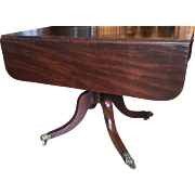 An early 19th century English breakfast / drop leaf mahogany table with solid brass claw feet. circa 1820.