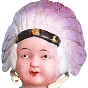 "This is an all bisque painted Indian doll that is 5-3/4"" tall with jointed arms and made in Japan.  Stamped in the bisque on the back are the words 'made in Japan'.  He has a purple head-dress, green and white shirt, blue pants and painted black shoe"