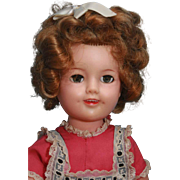 Shirley Temple doll by Ideal in vinyl marked and with flirty eyes and tagged pink dress.   Circa  1957-1961.