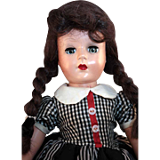"Hard plastic doll 18"" tall  from circa 1950's in good condition with brown human hair wig."