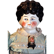 "Antique German china head doll with 1890's hairstyle that is 23"" tall."