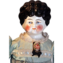 """Antique German china head doll with 1890's hairstyle that is 23"""" tall."""