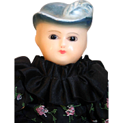 "Antique molded bonnet, glass eyed, wax over papier mache composition shoulder head doll 13"" tall in beautiful ruffled black print dress"