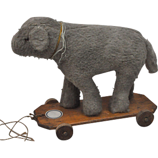 A French wool plush lamb on wheeled wooden platform, 1920s