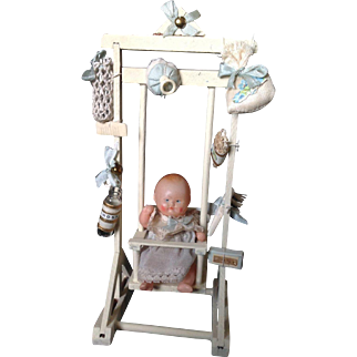French celluloid doll in swing with accessories