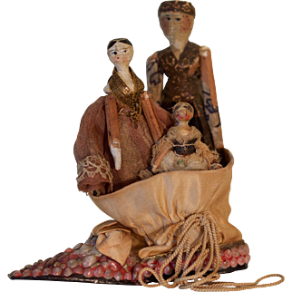 Three primitive Grodnertal dolls in a shell shoe