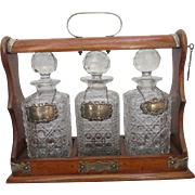 Good Edwardian Oak Silver plate Tantalus with Sterling Silver Decanter Labels