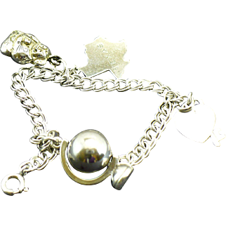 Vintage sterling charm bracelet with four sterling vintage charms