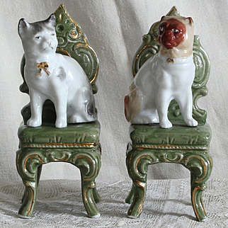 Two lovely german porcelain trinkets : a cat and a «Carlin» dog on a chair,perfect for a doll house.