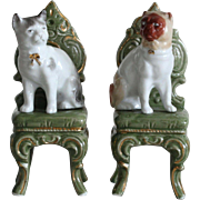 Two lovely german porcelain trinkets : a cat and a « Carlin » dog on a chair,perfect for a doll house.