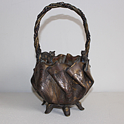 France circa 1900: Charming little hand-worked brass cache-pot in the form of a purse, with a cat and a small bulldog .