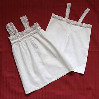 Set of two ancient French cotton doll' slips with lace suspenders.