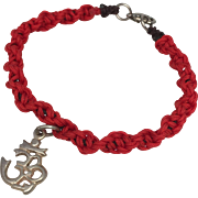 Sterling silver charm of an OM symbol with a red hand braided bracelet and sterling silver clasp