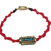 Sterling silver charm of a prayer wheel with turquoise inlaid and gold plated on a red hand braided bracelet, gold plated silver clasp