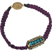 Sterling silver charm of a prayer wheel with turquoise inlaid and gold plated on a plum hand braided bracelet, gold plated silver clasp