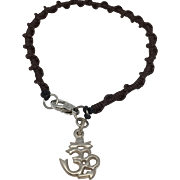 Sterling silver charm of an OM symbol with a brown color hand braided bracelet and sterling silver clasp
