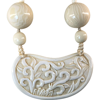 "Necklace made of hand carved floral design bone pendant, cream color resin beads and bone clasp. 24"" in length"