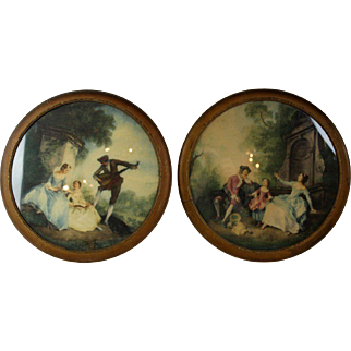 A pair of hand colored prints in round frames