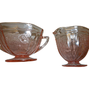 Matching pair of pink depression glass floral pattern sugar and creamer