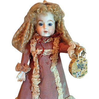 Gorgeous lady doll with a closed mouth and a stunning gown and matching hat with a golden bag.