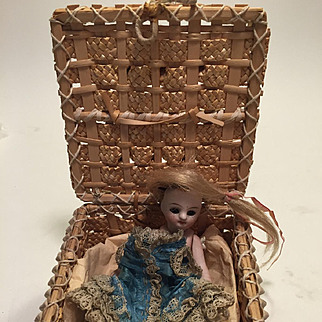 An Antique All Bisque Mignonette Child Doll, French c. 1880's, 4 inches, In Basket with Original Dress and Wig