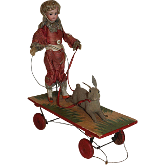 A Rare and Amusing Jumeau Mechanical Pull Along Toy, Boy Making Rabbit Jump through Hoop with Squeaker, French C. 1880's