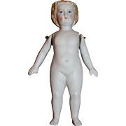 A Blonde Molded Hair All Bisque Doll, with Jointed arms, dressed. German c.1880's, 6 1/2 inches