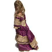 An Antique Small Wax Over Composition Doll wearing An Original Fabulous but Delicate Fashion  Dress