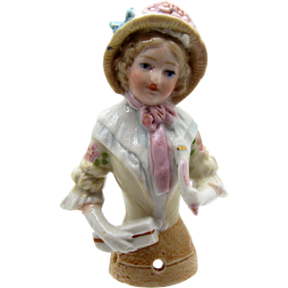 Antique Half Doll Wearing a Bonnet, Flowered Sleeves, Holidng a Fan and Package