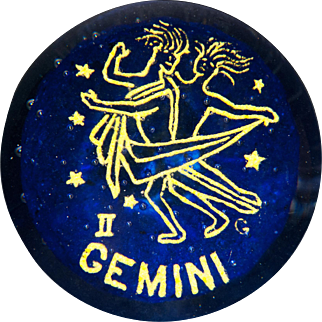Gentile Glass Gemini frit zodiac symbol over bubble studded blue ground glass paperweight.