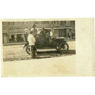 4 People in Model T, Variety store in Background 1920's RPPC Postcard