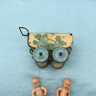 Vintage Tin plate pram with two celluloid babies.