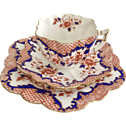 "Charles Wileman Imari teacup trio, ""Japan"" on daisy shape, 1899"