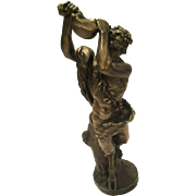 Antique Bronze Sculpture Of A Satyr Drinking Wine Against A Treetrunk