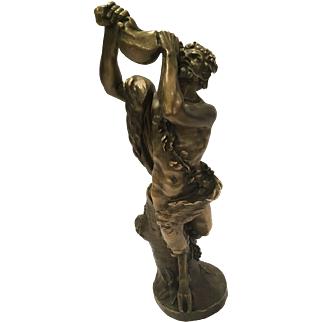 Bronze Sculpture Of A Satyr Drinking Wine Against A Treetrunk