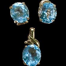 A classic blue topaz enhancer pendant with matching 14k oval cut blue topaz earrings.