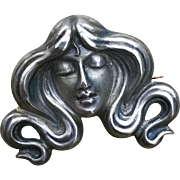 An absolutely charming art nouveau sterling lady face lapel pin