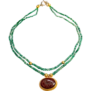 Two Strands of Natural Columbian Emeralds Support a Stunning Carnelian Intaglio Set in 18 Carat Gold