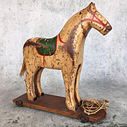Antique wooden toy horse, child's pull toy on metal wheeled base
